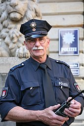 "A man wearing a blue shirt with the word ""POLIZEI"" written on it, Epaulets with 5 stars on them, and a blue peaked cap with a 12-pointed star on it. He is holding a radio."