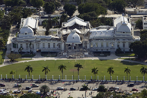 An aerial photograph of a white building with a green lawn and palm trees.  Onlooking are standing behind the white fence on the road.  The roof appears to have collapsed upon the story beneath and concert rumble is blocking the front steps.