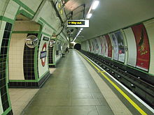 "View along a platform in a circular tunnel. Tracks run on the right side with the walls covered with cream and green tiles. An illuminated ""way out"" sign overhead indicates the exit."
