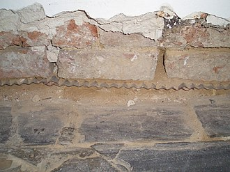 Damp proofing - A metal damp-proof course between the stone foundation and brick wall