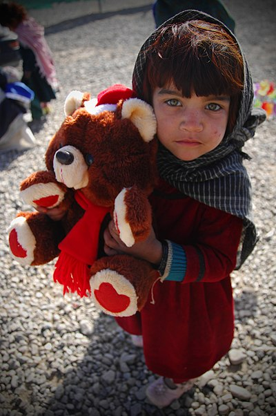 A young Afghan girl clenches a teddy bear that she received at a medical clinic at Camp Clark in Khost Province.