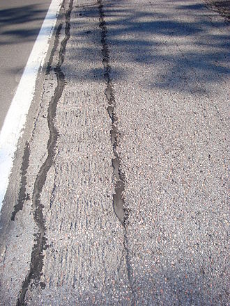 Rumble strip - An example of extensive cracking in rumble strips due to frost jacking on Interstate Highway 81 north of Syracuse.  These parallel cracks were sealed.  There were other sections with grass and weeds growing up through the rumble strip cracks
