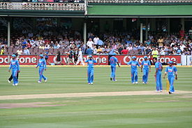 The view of a cricket field. Players wearing blue outfits can be seen.