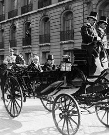 Zwart-witfoto van twee witharige besnorde individuen in een paardenkoets: de man rechts draagt een hoge hoed en kijkt vooruit;  de linker lacht naar de fotograaf;  op de achtergrond twee bewakers