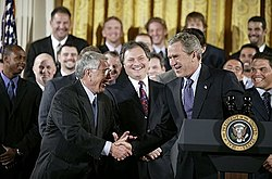 Two men in black suits shake hands smiling, the man on the right standing in front of a podium with the seal of the President of the United States on it.