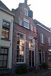 foto van Huis met gepleisterde in- en uitgezwenkte topgevel met vijf overhoekse pinakels