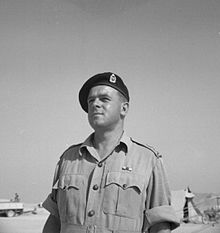 A black and white photograph of the head and shoulders of a man in a military uniform and beret. In the background is a tent and military vehicle