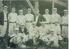 Group of 14 men. The majority are standing, while some in the front are sitting.
