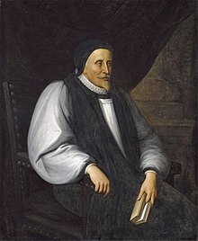 A solemn old white man clothed in Reformation-era clerical robes, seated and holding a book