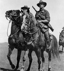 Black and white photo of a man wearing military uniform with a rifle slung across his back riding a horse. Two other similarly-dressed men are partly visible in the background.