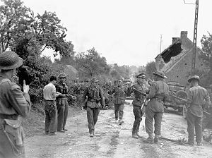 "South Alberta Regiment - Major David V. Currie (left, with pistol in hand) of the South Alberta Regiment accepting the surrender of German troops at Saint-Lambert-sur-Dives, France, 19 August 1944. This photo captures the very moment and actions that would lead to Major Currie being awarded the Victoria Cross. Battle Group Commander Major D.V. Currie at left supervises the round up of German prisoners. Reporting to him is trooper R. J. Lowe of ""C"" Squadron."