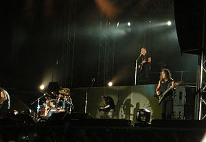 The four band members are shown performing during a concert