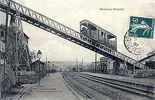 A sepia picture-postcard taken from a station platform, railway tracks running into the distance. Across the picture, an inclined elevated section (the funicular) runs, with a railcar midway along it.