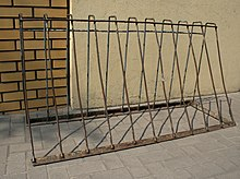A rusty metal A-frame with horizontal bars at the top and bottom joined by eleven vertical bars. It stands free on concrete in front of a join between a brick wall and a plaster wall.