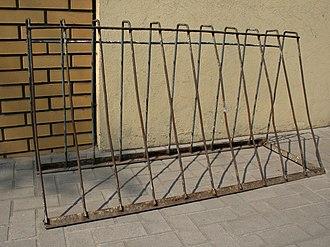 Ржавая металлическая А-образная рама с горизонтальными перекладинами вверху и внизу, соединенными одиннадцатью вертикальными перекладинами. Он стоит свободно на бетоне перед стыком между кирпичной стеной и штукатуркой.