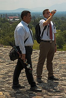 Two young men, the one on the left darker-skinned than the one on the right, who is drinking some orange liquid from a plastic bottle, standing on a stone surface with mountains in the background. They are both carrying backpacks and wearing white dress shirts, ties and slacks. The one on the right is wearing a short-sleeved shirt and tan slacks