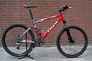 This mountain bicycle features oversized tires, a full-suspension frame, two disc brakes and handlebars oriented perpendicular to the bike's axis