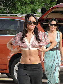 Identical female twins with long black hair are both walking towards the, one slightly in front of the other. The one in front is wearing a patterned, pastel colored crop top with black trousers, and is wearing her hair loose. The one behind is wearing a blue dress and has her hair tied back. Both are wearing sunglasses.