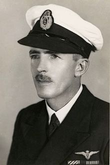 Head-and-shoulders portrait of man with moustache wearing dark-coloured jacket with black-and-white peaked cap}