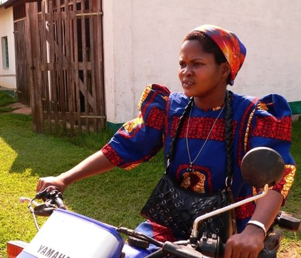 A sister of the Theresienne Sisters of Basankusu wearing a brightly coloured habit, riding a motor-bike, Democratic Republic of Congo, 2013 Nun on a motor-bike 2 - by Francis Hannaway.jpg