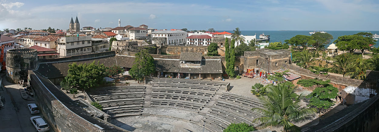 A panoramic photograph with an amphitheater surrounded by a castle wall in center.  The dull colors are interrupted by green trees and beyond the walls are white houses with red tiled roofs and a blue ocean.