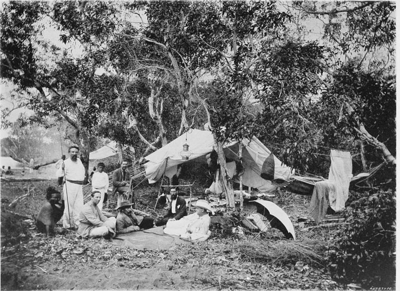 Black and white photograph of fly tent with group of Europeans and a few tribesman sitting, lounging or standing outside. Forested background.