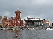 Red brick Victorian style building with clock tower and the Senedd, with water in foreground