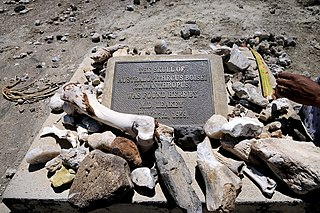 "Plinth with plaque sited in Olduvai Gorge marking the spot where Mary Leakey discovered ""Zinjanthropus"", the first-found A. boisei in Africa."