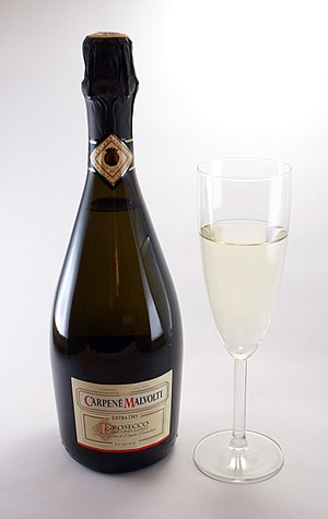 Prosecco - A bottle of Prosecco di Conegliano spumante extra dry and a glass of Prosecco frizzante, which stops forming bubbles soon after pouring