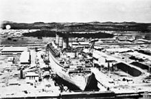 A large ship inside of a dry dock. The dry dock is surrounded by industrial buildings and hills are visible in the background