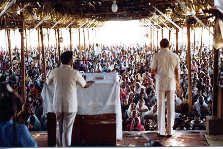 American pastor Johannes Maas preaching in Andhra Pradesh, India in 1974. Spreading the revival is an essential part of work done by evangelical missionaries. Revival crusade in Andhra Pradesh, India, Johannes Maas, American evangelist, speaking.jpg