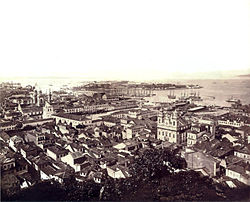 Photographic aerial view of the city from a hillside with ships at anchor in the harbor and island in the background