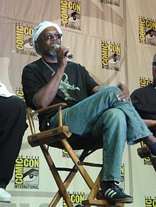 A man is sitting in a director's chair on a stage with two partially cropped out people sitting in the same type of chair on his left and right. The man is speaking into a microphone he is holding and is wearing tennis shoes, blue jeans, a black T-shirt with the film's poster image on it, sunglasses, and a white hat. In the background is a patterned design with the logo for Comic-Con.