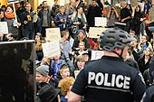 Crowd of protesters at Seattle–Tacoma International Airport. A police officer in a bicycle helmet is in the foreground; protesters sit and stand behind, many holding signs.