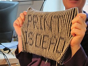 Illusion knitting - Shadow knitting viewed from the side, making the message knit into the fabric visible