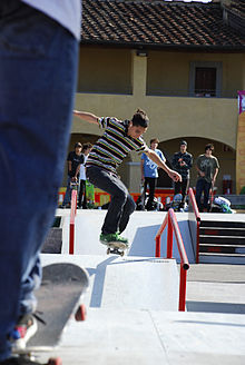 Skateboarder mentre affronta una cunetta.