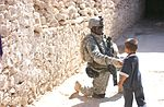 Spc. Nathan K. Edwards shakes the hand of a small boy DVIDS10475.jpg