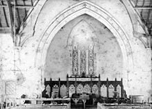 "Black and white photograph, originally on sensitized albumen, depicting the eastern end of the church interior. The lettering around the arch begins ""O Come Let Us Worship And Fall Down"", but the photographic materials used make the blue letters difficult to make out."