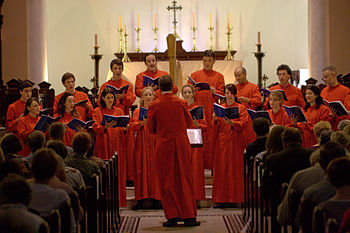 A photo of a red-robed choir in the chancel with the altar behind them. Candles and a brass cross are on the altar and the choirmaster is facing the singers with his back to the camera