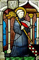 Stained glass image of a kneeling man with a halo holding an open book and a staff.