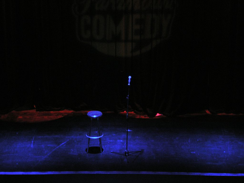 So here we see a dark stage and a stool and microphone.
