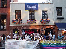A two-story building with brick on the first floor, with two arched doorways, and gray stucco on the second floor, off of which hang numerous rainbow flags.