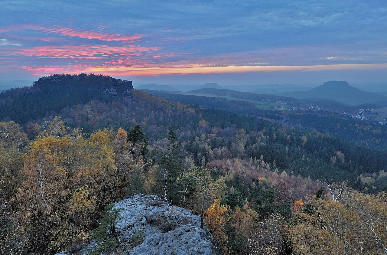 Coucher de soleil dans le parc national de la Suisse saxonne, en Allemagne. Vue depuis le sommet de la Papststein. Les trois grandes montagnes sont le mont  Gohrisch (à gauche), le mont  Königstein (au centre) et le mont Lilienstein (à droite). Le village s'appelle Gohrisch.  (définition réelle 2780×1831)
