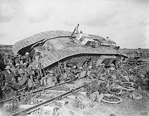 7th Infantry Brigade and Headquarters East - Men of the 20th (Service) Battalion, Manchester Regiment resting by a tank (serial number 9891), disabled by side-slipping down a railway embankment, near Premont, 8 October 1918.