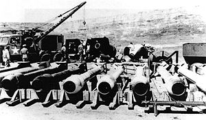 "Silverplate - ""Thin Man"" plutonium gun test casings at Wendover Army Air Field. Casing designs for ""Fat Man"" bombs are seen in the background. The tow truck was used to lower bombs into a pit for loading into the aircraft."