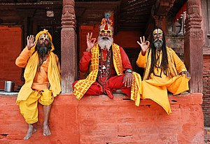Three Saddhus sitting on the Vishnu Temple of Kathmandu's Durbar Square, Nepal, performing the vitarka mudrā.