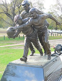 "Statue outside the MCG of Wills umpiring the 1858 game between Melbourne Grammar and Scotch College. The plaque reads that Wills ""did more than any other person--as a footballer and umpire, co-writer of the rules and promoter of the game--to develop Australian football during its first decade."" Tom wills statue.jpg"