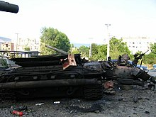 Burned tank amid other debris