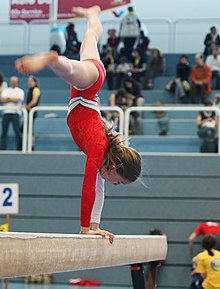 A girl performs a cartwheel on the gymnastics beam