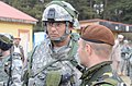U.S. Army Maj. Russell Thomas, left, the executive officer of Fires Squadron, 2nd Cavalry Regiment, talks with a Romanian soldier role-playing as an Afghan Uniform Police officer during a mission rehearsal 130310-A-OY175-001.jpg